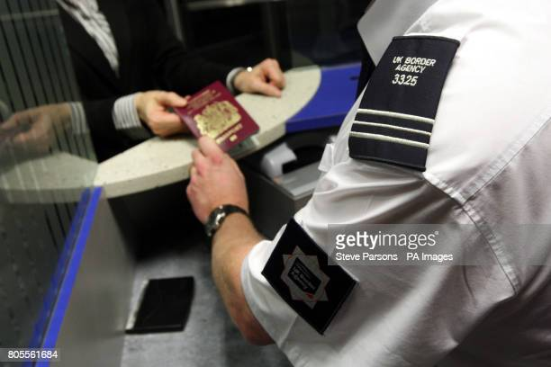 Border Agency officer checks a passport in the North Terminal of Gatwick Airport Sussex