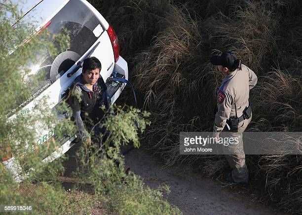 A border agent guards an immigrant after he was captured near the USMexico border on August 15 2016 near Mission Texas Border security has become a...