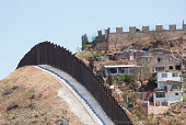"""The new steel beam border fence overlooks Nogales, Mexico.  Since this section of new 18 foot tall fence has been completed in 2011, officials have cut the number of aliens entering the United States"