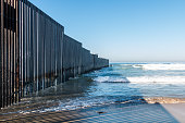Border Field State Park beach in San Diego, California with the international border wall separating the United States from Tijuana, Mexico.