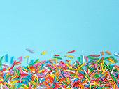 Border frame of colorful sprinkles on blue background with copyspace. Top view or flat lay