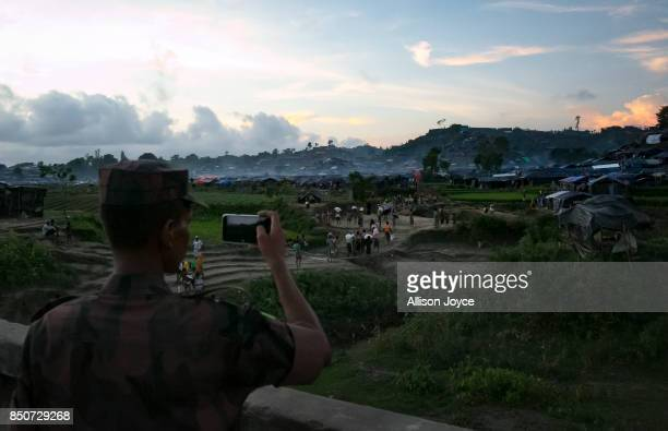 COX'S BAZAR BANGLADESH SEPTEMBER 21 A border guard takes a photo overlooking the Unchiprang Rohingya refugee camp on September 21 2017 in Cox's Bazar...