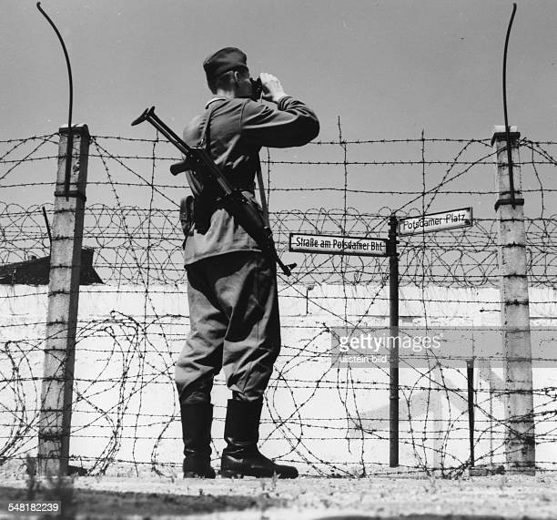 A border guard with binoculars in front of the Berlin Wall near Potsdamer Platz 1964