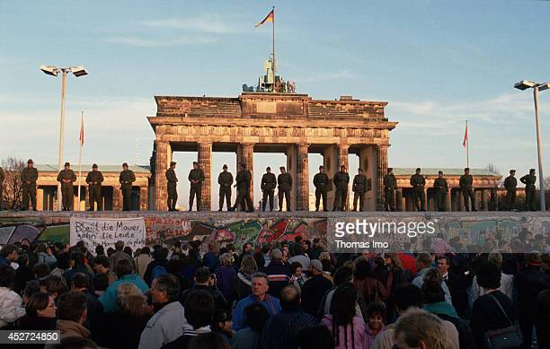 Border guards of the German Democratic Republic standing on the Berlin Wall observing demonstrating people on November 09 in Berlin Germany The year...