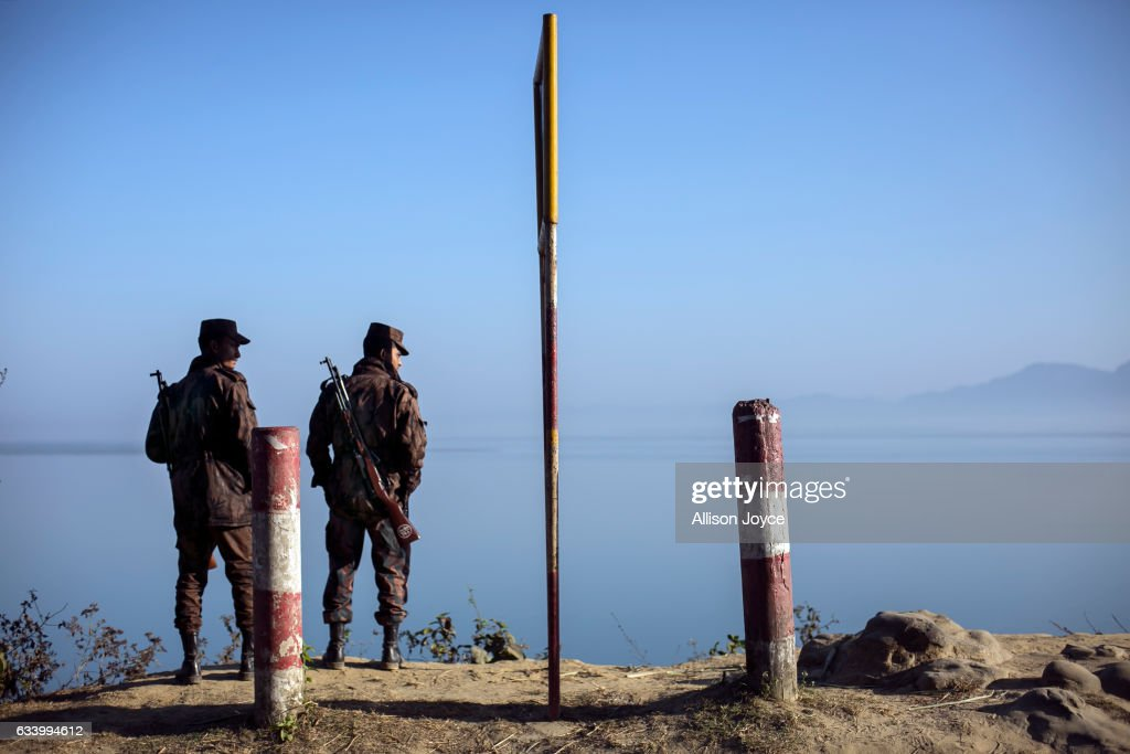 Border guards stand near the edge of the Naf river which separates Myanmar from Bangladesh is seen on February 6, 2017 in Teknaf, Bangladesh. The United Nations estimates about 69,000 Rohingya Muslims have fled to Bangladesh from Myanmar since October last year, after the Burmese army launched a campaign it calls 'clearance operations' in response to an attack on border police on October 9, believed to have been carried out by Rohingya militants. Waves of Rohingya civilians have since fled across the border, most living in makeshift camps and refugee centers with harrowing stories on the Burmese army committing human-rights abuses, such as gang rape, arson and extrajudicial killing. The Rohingya, a mostly stateless Muslim group numbering about 1.1 million, are the majority in Rakhine state and smaller communities in Bangladesh, Thailand and Malaysia. The stateless Muslim group are routinely described by human rights organizations as the 'most oppressed people in the world' and a 'minority that continues to face statelessness and persecution.'