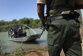 S Border Patrol agent Alvin Normandia waits for colleagues to dock at a landing point on the US side of the Rio Grande River across from Mexico...