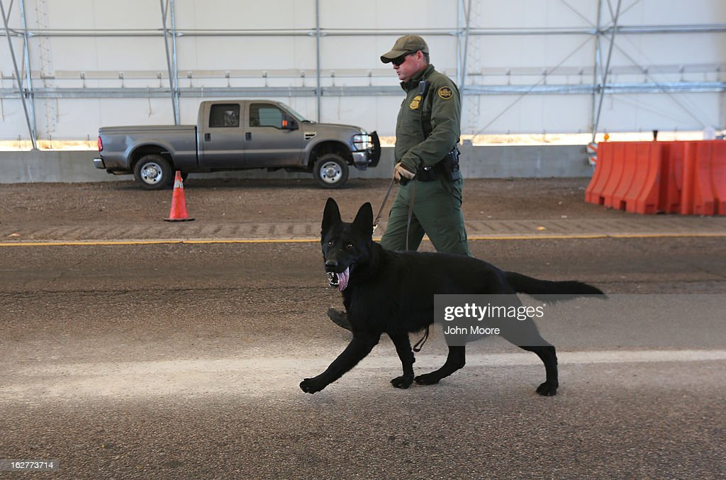 S. Border Patrol agent and drug sniffing German Shepherd, Jack-D, prepare to search vehicles for drugs at a checkpoint near the U.S.-Mexico border on February 26, 2013 north of Nogales, Arizona. Border Patrol agents use canines to detect illegal drugs crossing north from Mexico.