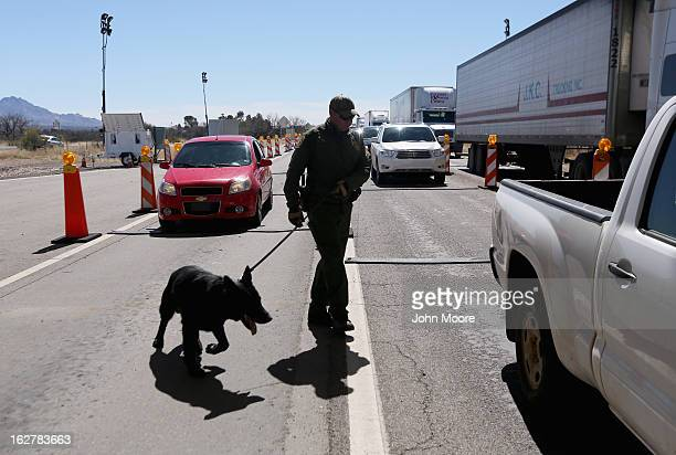 S Border Patrol agent and drug sniffing German Shepherd JackD prepare to search vehicles for drugs at a checkpoint near the US Mexico border on...