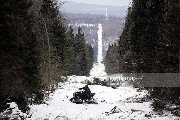 S Border Patrol Agent Andrew Mayer rides a ATV as he looks for signs of illegal entry along the boundary marker cut into the forest marking the line...