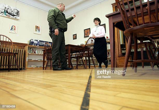 S Border Patrol Agent Andrew Mayer speaks to Nancy Rumery as he stands on the Canadian side of a line on the floor of the Haskell Free Library and...