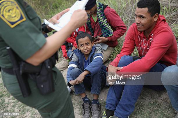 S Border Patrol agent checks birth certificates while taking Central American immigrants into detention on January 4 2017 near McAllen Texas...