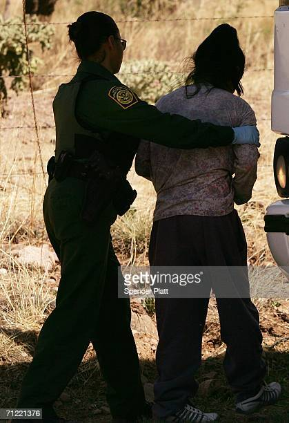 S Border Patrol agent detains a woman caught after illegally crossing the border with Mexico June 16 2006 in Pima County Arizona President George W...