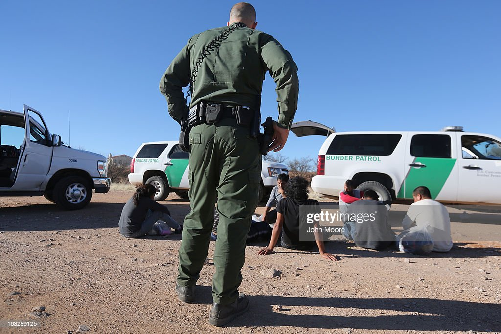 S. Border Patrol agent guards a group of Mexican immigrants caught after they crossed into the United States on March 6, 2013 near Walker Canyon, Arizona. Due to broad federal sequestration budget cuts, Border Patrol agents are expected to begin taking unpaid furlough days in April, as Customs and Border Protection funding is expected to be reduced by more than $500 million.