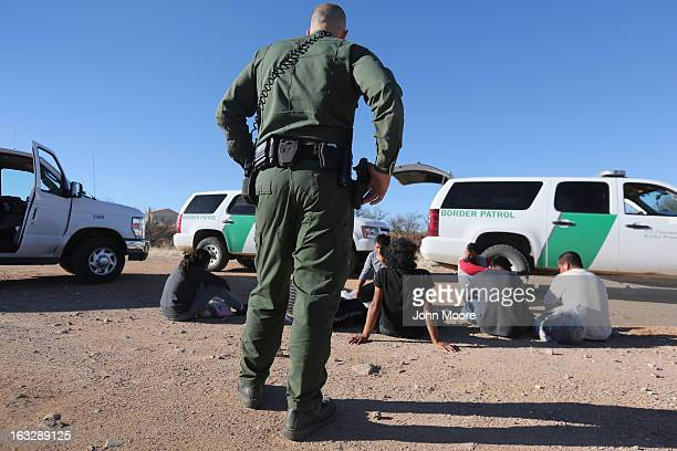 S Border Patrol agent guards a group of Mexican immigrants caught after they crossed into the United States on March 6 2013 near Walker Canyon...