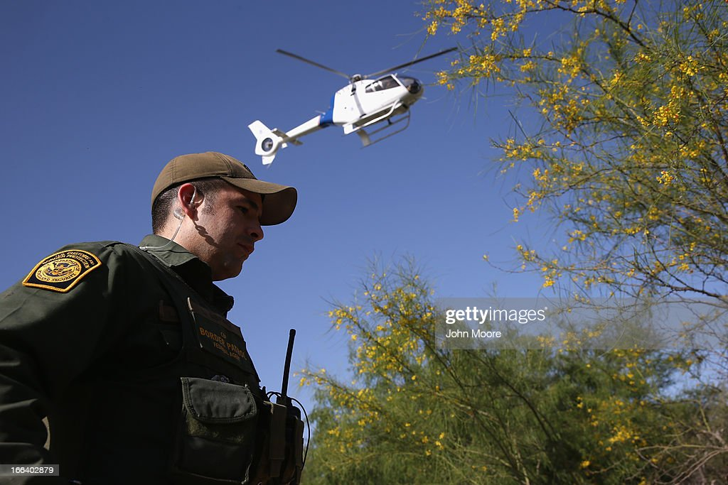 S. Border Patrol agent guards a suspected drug smuggler caught along the Rio Grande River on April 11, 2013 in Mission, Texas. A smuggling mission was broken up by U.S. Border Patrol agents with helicopter support from the Office of Air and Marine. In addition to the drug smuggling, Border Patrol agents say they have also seen an additional surge in immigrant traffic in Texas' Rio Grande Valley sector since immigration reform negotiations began this year in Washington D.C.