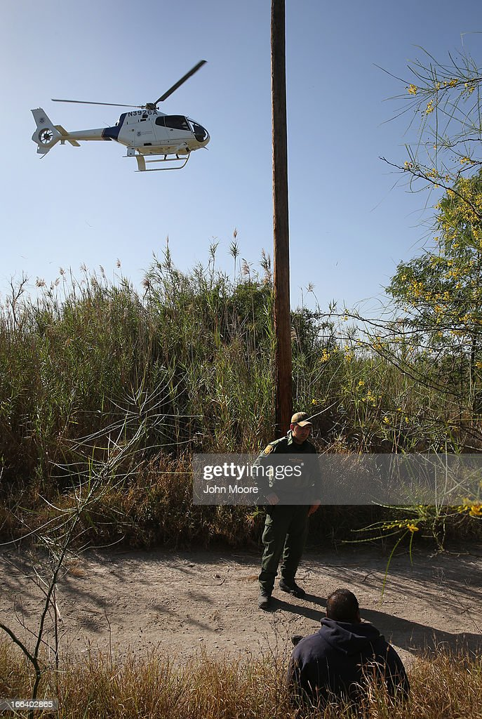 S. Border Patrol agent guards a suspected drug smuggler on April 11, 2013 in Mission, Texas. Border Patrol agents with helicopter support from the Office of Air and Marine broke up a smuggling shipment of marijuana being transported across the border from Mexico into Texas. In addition to heavy drug smuggling in the area, Border Patrol agents say they have also seen an additional surge in immigrant traffic in Texas' Rio Grande Valley sector since immigration reform negotiations began this year in Washington D.C.