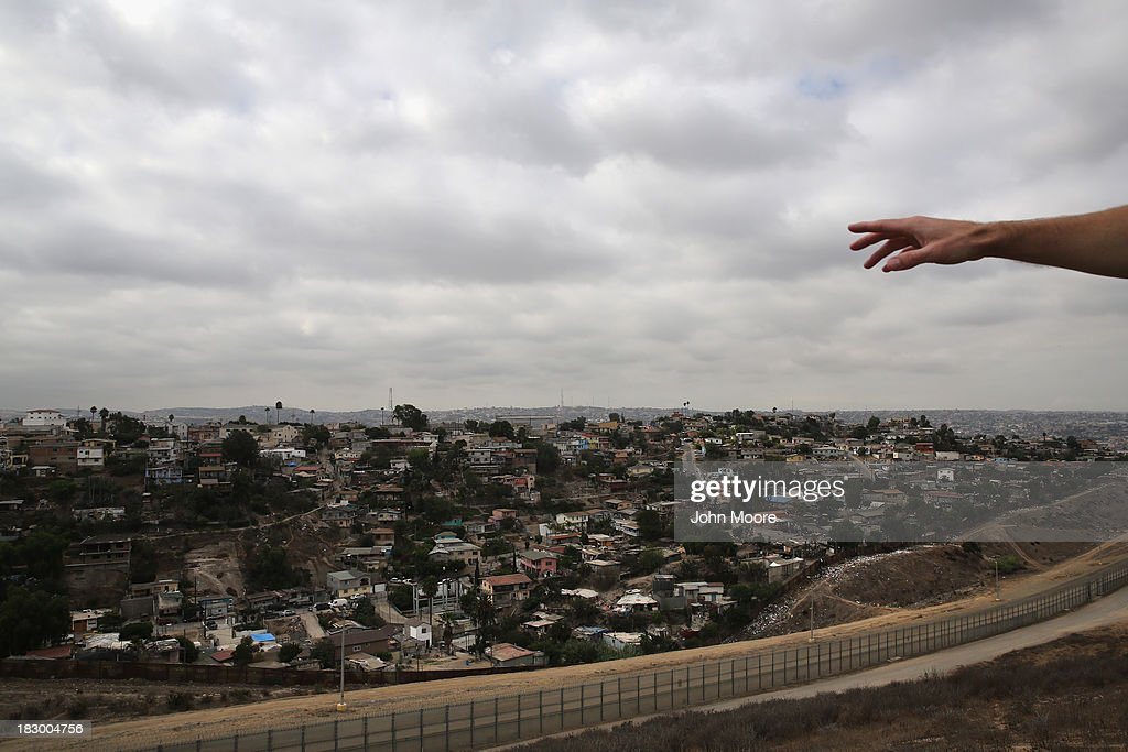 U.S. Border Patrol agent Jerry Conlin describes smuggling activities from Tijuana, Mexico while near the U.S.-Mexico border fence on October 3, 2013 near San Diego, California. While hundreds of thousands of government workers were furloughed due to the federal shutdown, thousands of Border Patrol agents, air-traffic controllers, prison guards and other federal employees deemed 'essential' remain on duty, although their pay may be delayed.
