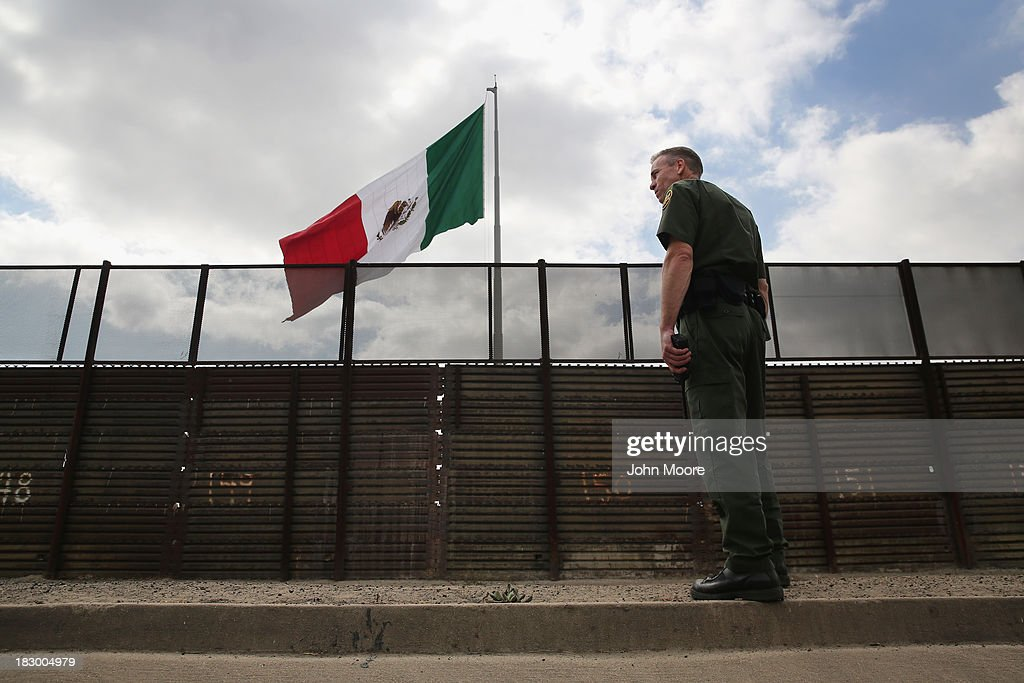 U.S. Border Patrol agent Jerry Conlin stands on the American side of the U.S.-Mexico border fence on October 3, 2013 at San Ysidro, California. While hundreds of thousands of government workers were furloughed due to the federal shutdown, thousands of Border Patrol agents, air-traffic controllers, prison guards and other federal employees deemed 'essential' remain on duty, although their pay may be delayed.