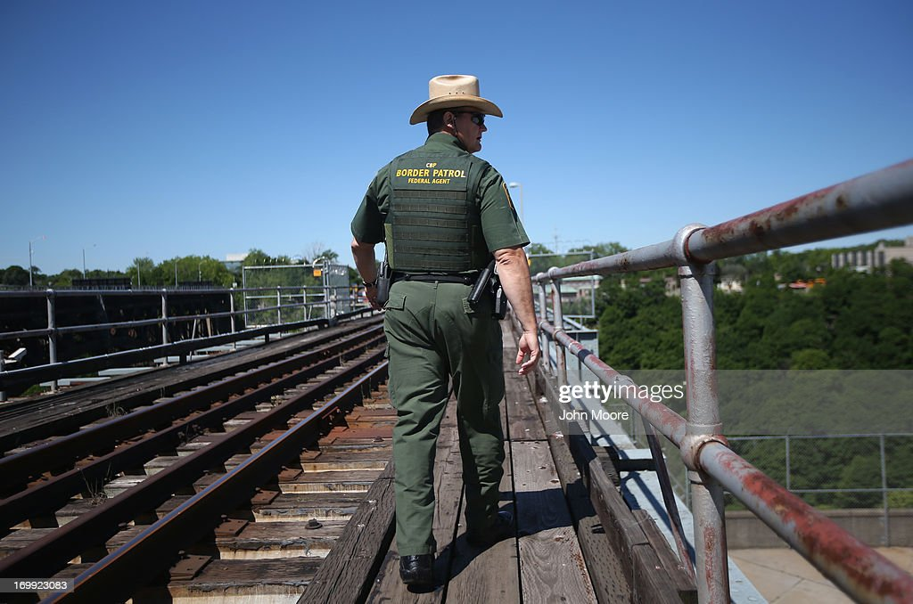 U.S. Border Patrol agent John Stanko walks along a rail bridge connecting the U.S. with Canada on June 4, 2013 near Black Rock, New York. U.S. Border Patrol agents monitor the bridge for undocumented immigrants trying to cross either into or out of the United States illegally on the bridge.