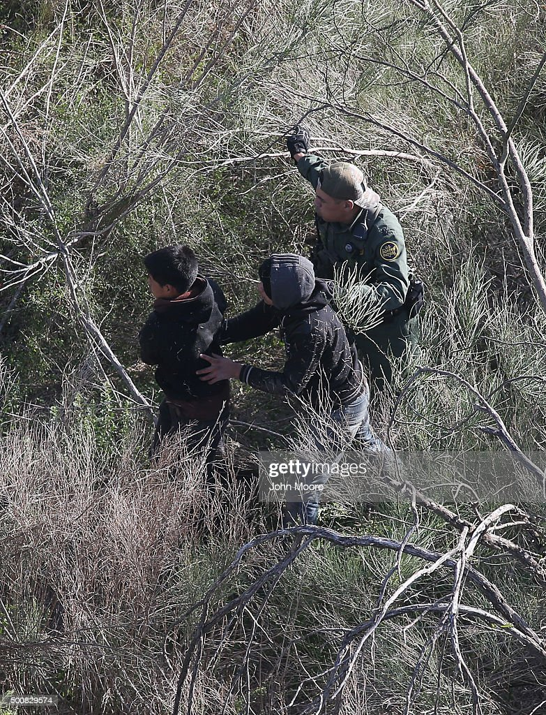 S. Border Patrol agent leads juvenile undocumented immigrants out of thick brush after capturing them near the U.S.-Mexico border on December 10, 2015 at La Grulla, Texas. The number of families and unaccompanied minors from Central America illegally crossing the border into Texas' Rio Grande Valley has surged in recent months. Border security remains a key issue in the U.S. Presidential campaign.