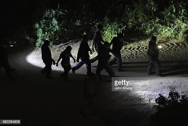 S Border Patrol agent leads of group of captured undocumented immigrants near the USMexico border late on August 19 2016 near Hidalgo Texas Air...