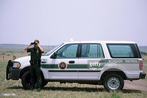 Border Patrol agent looking through binoculars.