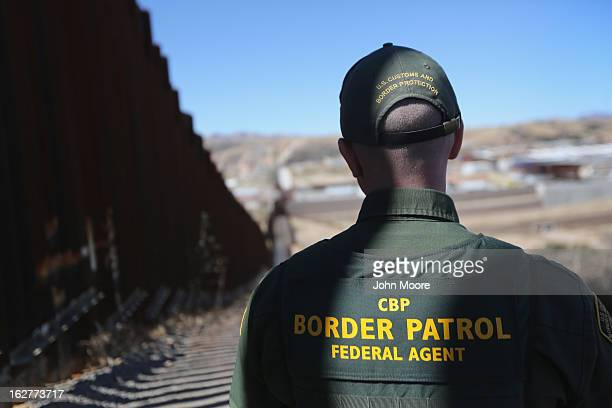 S Border Patrol agent looks along a section of the recentlyconstructed fence at the USMexico border on February 26 2013 in Nogales Arizona The new...
