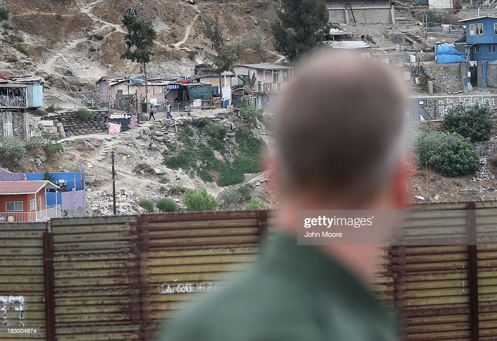 S. Border Patrol agent looks into Tijuana, Mexico from the American side of the U.S.-Mexico border fence on October 3, 2013 near San Diego, California. While hundreds of thousands of government workers were furloughed due to the federal shutdown, thousands of Border Patrol agents, air-traffic controllers, prison guards and other federal employees deemed 'essential' remain on duty, although their pay may be delayed.