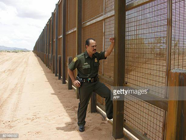 US Border Patrol Agent Martin Hernandez stands at the five meter tall border security fence July 11 2008 at the Santa Teresa Port of Entry in New...