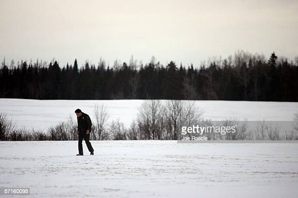S Border Patrol Agent Mike Clark follows foot prints of a possible illegal alien through a field towards the Canadian border March 22 2006 in Norton...