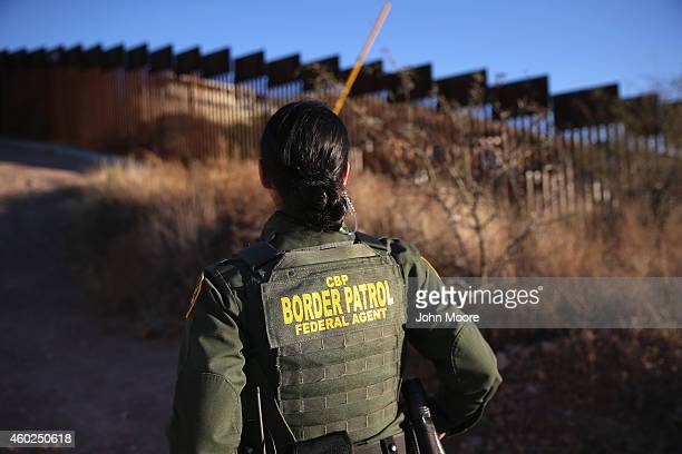 S Border Patrol agent Nicole Ballistrea watches over the USMexico border fence on December 9 2014 in Nogales Arizona With increased manpower and...
