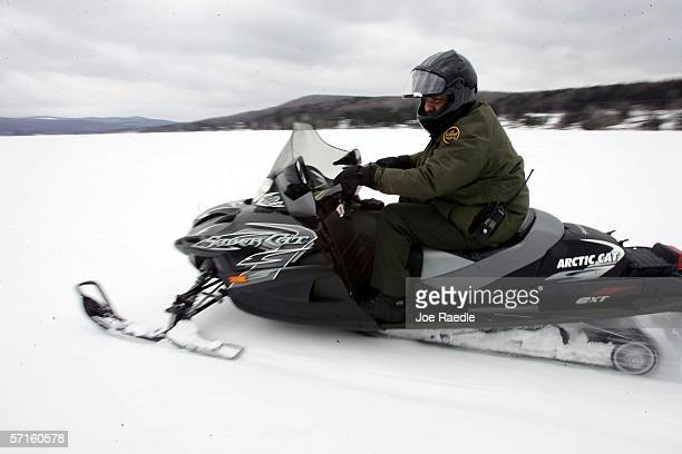 S Border Patrol Agent Paul Mulcahy rides a snowmobile while looking for signs of illegal aliens during a patrol on a frozen lake that splits the...