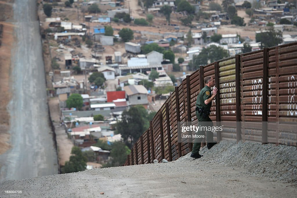 S. Border Patrol agent peers in Mexico through the U.S.-Mexico border fence on October 3, 2013 in San Diego, California. The fence is double in some areas, while it often ceases altogether in deep ravines or mountainous areas. While hundreds of thousands of government workers were furloughed Tuesday, thousands of Border Patrol agents, air-traffic controllers, prison guards and other federal employees deemed 'essential' remain on duty, although their pay may be delayed.