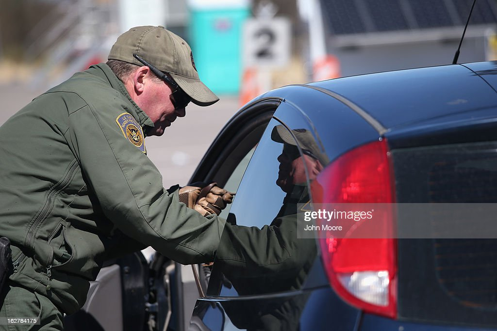 S. Border Patrol agent prepares to search a car entering the United States from Mexico on February 26, 2013 in Nogales, Arizona. Some 15,000 people cross between Mexico and the U.S. each day in Nogales, Arizona's busiest border crossing.