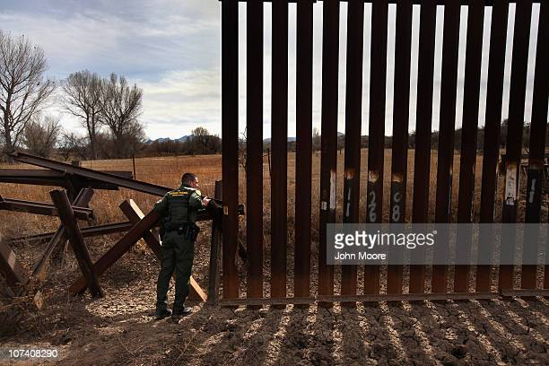 S Border Patrol agent Richard Funke inspects the juction of the new and old border fence at the US Mexico border on December 7 2010 near Nogales...