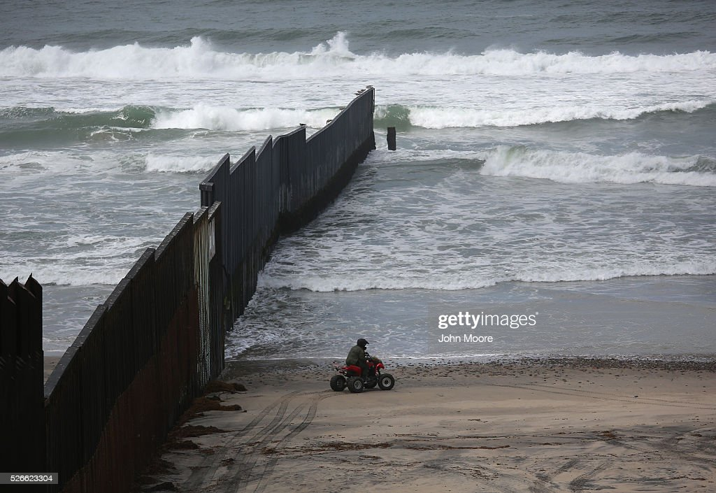 S. Border Patrol agent rides the beach at the U.S.-Mexico border fence on April 30, 2016 into San Diego, California. Five families, with some members living in Mexico and others in the United States, were permitted to meet and embrace for three minutes each at a door in the fence, which the U.S. Border Patrol opened to celebrate Mexican Children's Day. It was only the third time the fence, which separates San Diego from Tijuana, had been opened for families to briefly reunite.