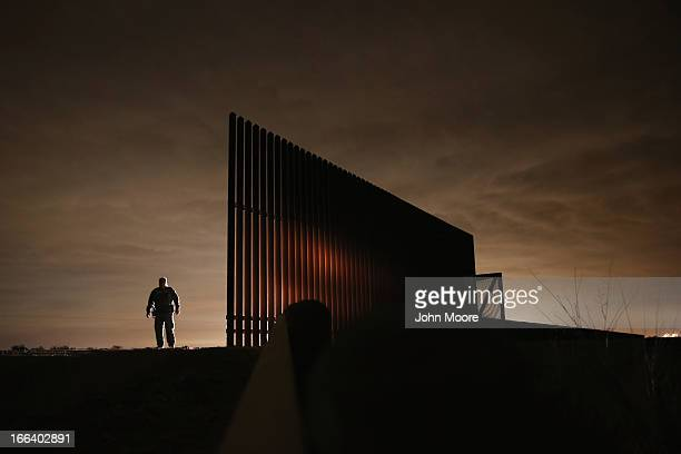 S Border Patrol agent Sal De Leon stands near a section of the US Mexico border fence while stopping on patrol on April 10 2013 in La Joya Texas...