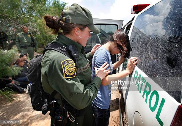 Border Patrol agent searches an undocumented immigrant apprehended near the Mexican border on May 27 2010 near McAllen Texas The woman was captured...