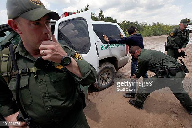 Border Patrol agent searches an undocumented immigrant apprehended near the Mexican border on May 27 2010 near McAllen Texas The man was captured...