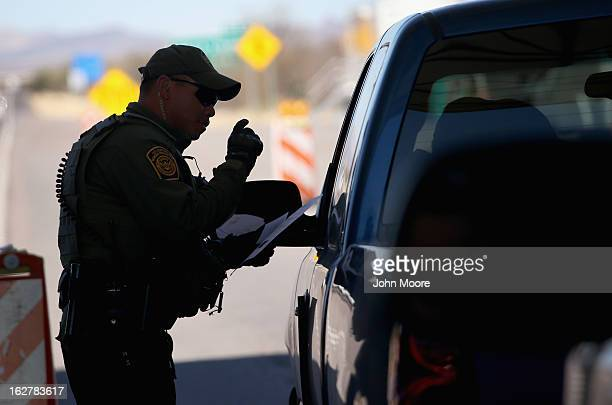 S Border Patrol agent speaks to a driver at a checkpoint from Mexico into the United States on February 26 2013 north of Nogales Arizona Some 15000...