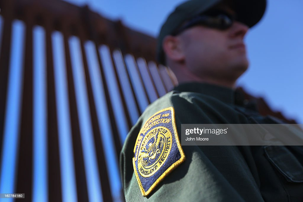 S. Border Patrol agent stands at the U.S.-Mexico border fence on February 26, 2013 in Nogales, Arizona. Various federal agencies are tasked with securing the border from drug smugglers and illegal immigration in the Tucson sector of Arizona.