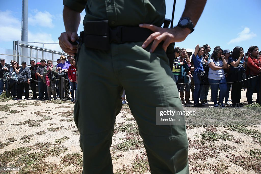 S. Border Patrol agent stands guard as families prepare to meet loved ones at the U.S.-Mexico Border fence during a 'Opening the Door of Hope' event on April 30, 2016 in San Diego, California. Five families, with some members living in Mexico and others in the United States, were permitted to meet and embrace for three minutes each at a door in the fence, which the U.S. Border Patrol opened to celebrate Mexican Children's Day. It was only the third time the fence, which separates San Diego from Tijuana, had been opened for families to briefly reunite. The event was planned by the immigrant advocacy group Border Angels.