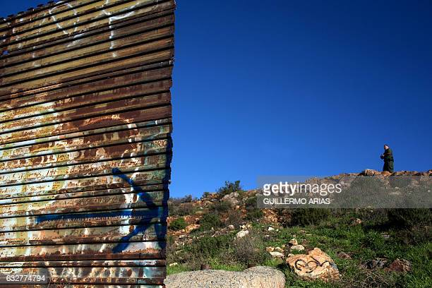 A Border Patrol agent stands guard at the end of the urban fencing along the US Mexico border at El Nido del Aguila on the outskirts of Tijuana on...