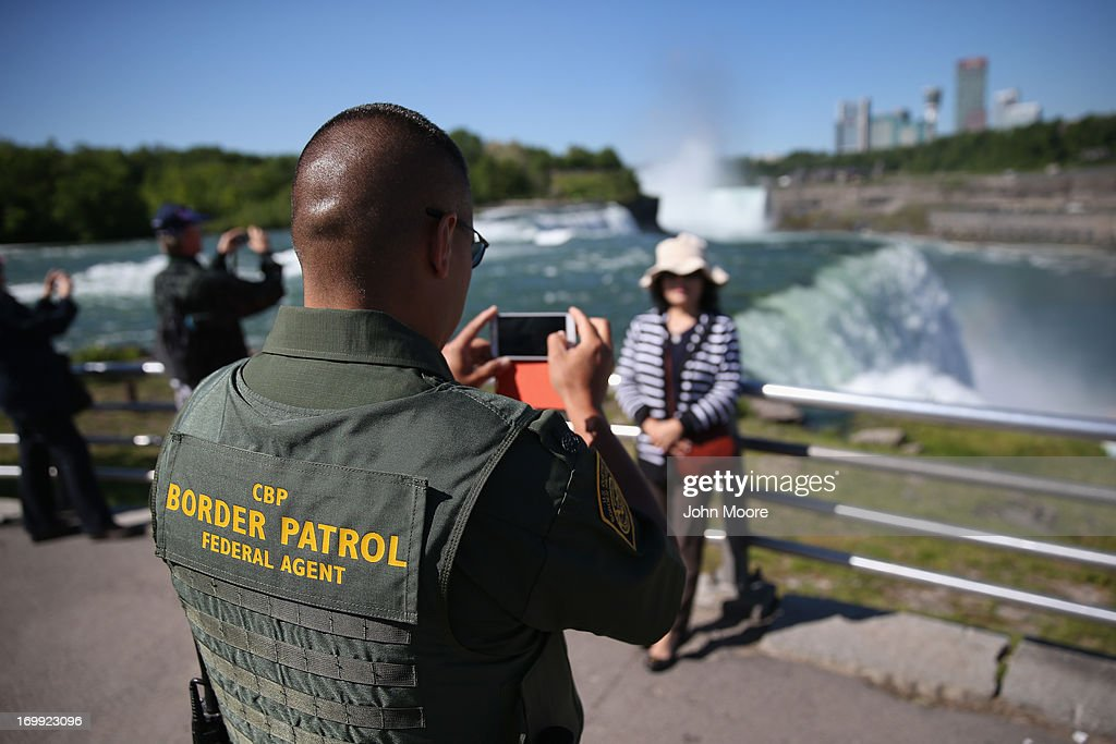 S. Border Patrol agent takes a snapshot for a tourist in front of Niagara Falls on June 4, 2013 in Niagara Falls, New York. The falls, which lie directly on the U.S.-Canada border, are a major destination for American and international tourists alike. Border Patrol agents detain foreign travelers who have overstayed their visas as well as undocumented immigrants who attempt to illegally cross the international bridge in Niagara Falls.