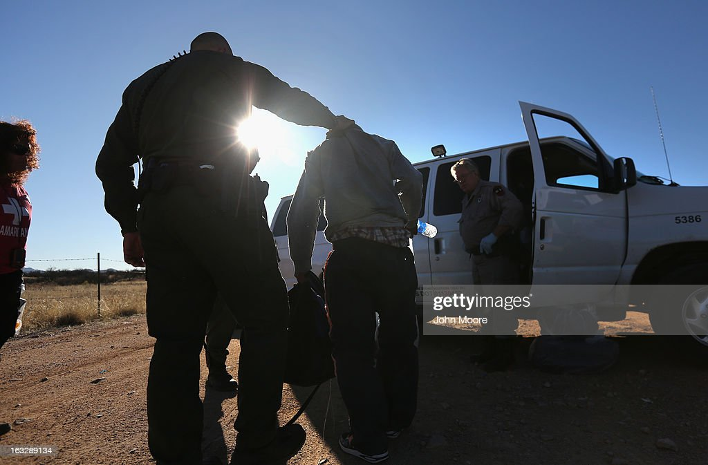 S. Border Patrol agent takes an immigrant into custody after his group of eight Mexicans was caught while crossing illegally into the United States on March 6, 2013 near Walker Canyon, Arizona. Due to broad federal sequestration budget cuts, Border Patrol agents are expected to begin taking unpaid furlough days in April, as Customs and Border Protection funding is expected to be reduced by more than $500 million.