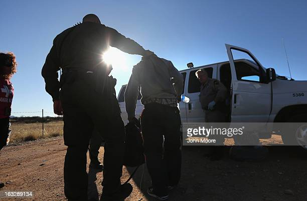 S Border Patrol agent takes an immigrant into custody after his group of eight Mexicans was caught while crossing illegally into the United States on...