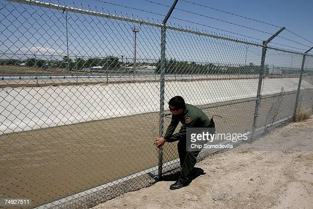 S Border Patrol agent tries to close a hole that had just been cut in a fence along the USMexico border June 26 2007 in El Paso Texas Border Patrol...