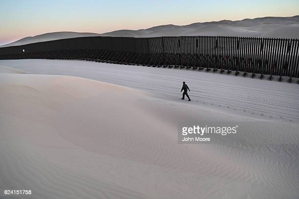S Border Patrol agent walks along the USMexico border at the Imperial Sand Dunes on November 17 2016 near Felicity California The 15foot border fence...