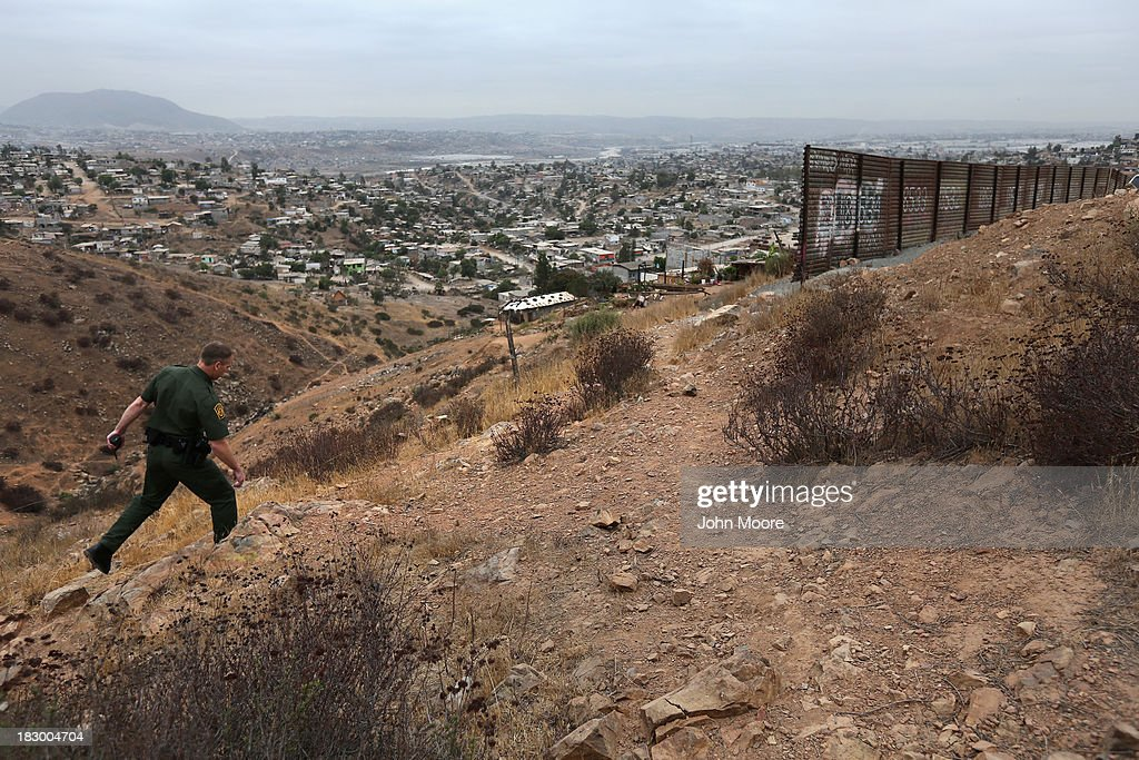 S. Border Patrol agent walks near a part of the U.S.-Mexico border fence on October 3, 2013 near San Diego, California. The fence is double in some areas, while it often ceases in deep ravines or mountainous areas. While hundreds of thousands of government workers were furloughed Tuesday, thousands of Border Patrol agents, air-traffic controllers, prison guards and other federal employees deemed 'essential' remain on duty, although their pay may be delayed.