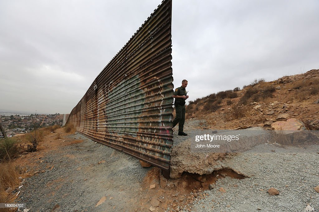 S. Border Patrol agent walks past a part of the U.S.-Mexico border fence on October 3, 2013 near San Diego, California. The fence is double in some areas, while it often ceases in deep ravines or mountainous areas. While hundreds of thousands of government workers were furloughed Tuesday, thousands of Border Patrol agents, air-traffic controllers, prison guards and other federal employees deemed 'essential' remain on duty, although their pay may be delayed.